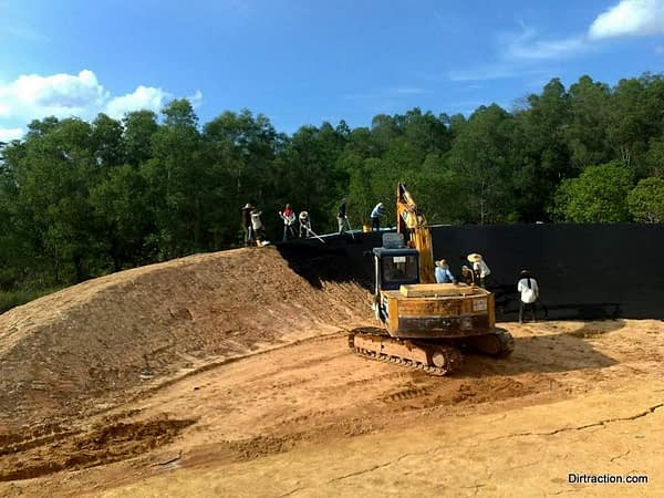 excavator assisted asphalt laying